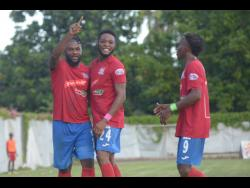 Dumbeholden's goalscorer Dean Andre Thomas (centre) celebrates with teammates Andre McFarlane (left)  and Demario Phillips after finding the back of the net against UWI FC on Sunday.