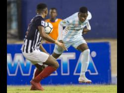 Chantomoi Taylor (right) of St George's College tries to go past  Nathan Hunter of Jamaica College in the semi-final of the Manning Cup in 2018.