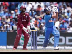 Windies wicketkeeper Nicholas Pooran (left) looks on as India's Rohit Sharma is dismissed during a Twenty20 International match in Lauderhill, Florida, on Saturday, August 3, 2019.
