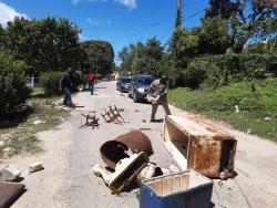 Cops attached to the Trelawny police clear derbis from sections of the Wakefield and Friendship main roads in Trelawny after residents blocked them to protest the shooting death of an elderly resident last Friday night.