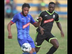Molynes United's Shane Watson (right) tracks the movement of Dunbeholden's Dean-Andre Thomas during their Red Stripe Premier League game at the Constant Spring Field on Sunday, December 29, 2019.