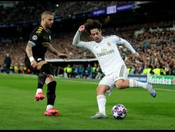 In this file photo dated Wednesday, February 26, 2020, Real Madrid's Isco (right) duels for the ball with Manchester City's Kyle Walker during the Champions League, round of 16, first leg match between Real Madrid and Manchester City at the Santiago Bernabeu stadium in Madrid, Spain.