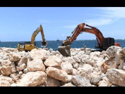Heavy machinery manoeuvre boulders along the Kingston waterfront in the vicinity of the Rae Town fishing village. A multimillion-dollar shoreline protection wall, or stone guard, is being constructed as a buffer against sea surges.
