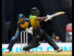 Rovman Powell (right) of Jamaica Tallawahs hits 4 as Andre Fletcher of St Lucia Zouks watch during the Hero Caribbean Premier League match 3 between Jamaica Tallawahs  and  St Lucia Zouks at Brian Lara Cricket Academy on August 19, 2020