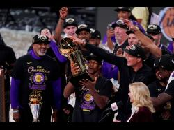 Los Angeles Lakers' Rajon Rondo (second left) holds the trophy as he celebrates with his teammates after the Lakers defeated the Miami Heat 106-93 in Game 6 of the  NBA Finals on Sunday, October11.