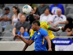 Curaçao midfielder Michael Maria (front) and Jamaica midfielder Andre Lewis try to head the ball in a Concacaf Gold Cup match in June 2019 in Los Angeles.