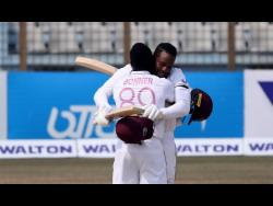 Nkrumah Bonner embraces Kyle Mayers during their 216-run fourth-wicket partnership on the final day of the first Test match against Bangladesh yesterday.