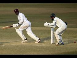 West Indies batsman Nkrumah Bonner plays a shot down the leg side as Bangladesh wicket-keeper Liton Das looks on during the second inning of the first Test on February 7, 2021.