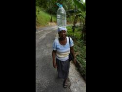 Emelyn Banton makes her way home after another of her daily trips to fetch water in Aberdeen square, St Elizabeth.