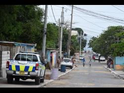 Police keeping a watch on Fourth Street in Trench Town.