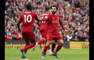 Liverpool's Mohamed Sala (right) celebrates with his teammate Sadio Mane after scoring his side's opening goal during their English Premier League match against Bournemouth at Anfield Stadium in Liverpool, England, on Saturday, March 7, 2020.
