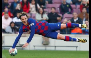 Barcelona's Antoine Griezmann falls during a Spanish La Liga match against Eibar at the Camp Nou stadium in Barcelona, Spain.