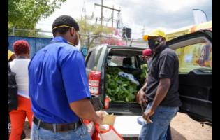 President of the Kingston and St Andrew Association of Branch Societies (ABS) of the Jamaica Agricultural Society (JAS), Albert Green (right) sells pak choi to customer Roje Miller.