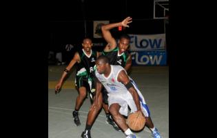 File In this file photo from August 16, 2013, an Urban Knights player (front) is challenged by two Spanish Town Spartans opponents during game two of the FLOW National Basketball League finals at the National Stadium Court.
