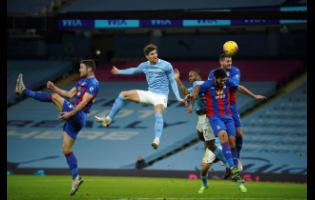 Manchester City's John Stones (centre), heads the ball to score his side's opening goal during an English Premier League football match between Manchester City and Crystal Palace at the Etihad Stadium in Manchester, England,  yesterday.