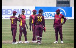 Left-arm spinner Akeal Hosein (second left) is congratulated by captain Jason Mohammed after taking a wicket for the West Indies against hosts Bangladesh in the opening One-Day International in Dhaka yesterday.