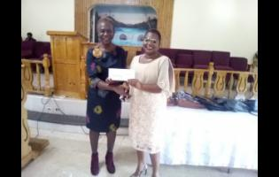 Pauline Beecher (left) presents a cheque to Simon Primary and Infant School principal Nova-Dean Samuels-Lee.