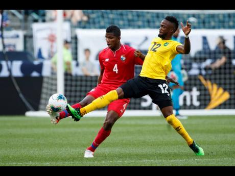 Panama's Fidel Escobar (left) and Jamaica's Junior Flemmings battle for the ball during the first half of a Concacaf Gold Cup match on June 30, 2019.