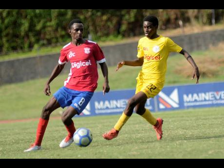 Altiman Gordon (left) of Camperdown High School eases past Rayon Maxwell of Charlie Smith High School during their ISSA/ Digicel Manning Cup match at Stadium East field yesterday.