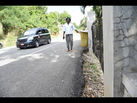 Some residents have difficulty accessing their homes following the acquisition of their lands to accommodate the road expansion. Buelah Morgan, for example, steps out of her yard and on to the roadway.