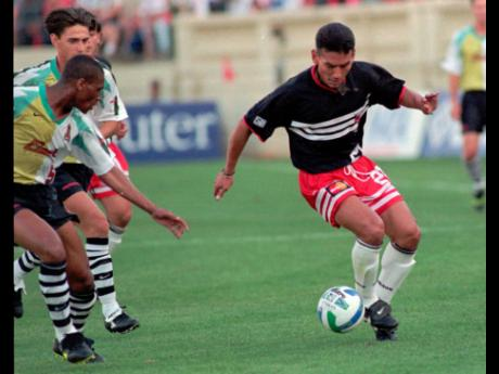 In this April 6, 1996 file photo, D.C. United forward Raul Diaz Arce, of El Salvador, moves the ball downfield against San Jose Clash defenders Michael Emenalo (left) from Nigeria, and Victor Mella, partially obscured, from Chile, during first half of the inaugural MLS game at San Jose, California.