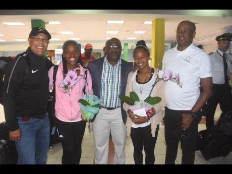 Match officials Princess Brown (second left) and Stephanie-Dale Yee Sing (second right) are greeted by FIFA referee instructor Peter Prendergast (left), Jamaica Football Federation (JFF) general secretary Dalton Wint (centre) and JFF Referees Department manager Victor Stewart on arrival at the Norman Manley International Airport in Kingston on July 8, 2019 after they officiated at the 2019 FIFA Women's World Cup in France.