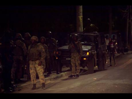 Members of the Jamaica Defence Force in Denham Town, west Kingston, where one of its patrol vehicles was involved in a crash last night.