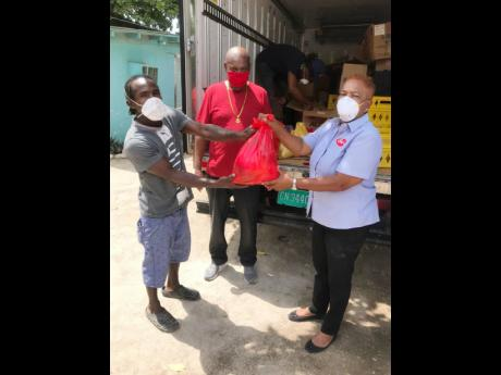 Carol Ivey, promotions manager, Cal's Manufacturing Limited make a presentation to two of the grooms at Caymanas Park yesterday.