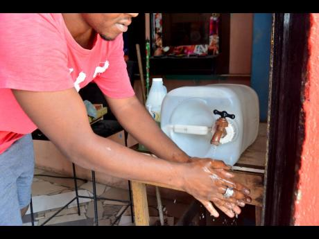 A customer washes his hands at the sanitisation station outside of Kenisha's Place in the Waltham Park area.
