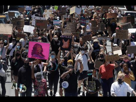 A crowd marches in San Francisco, California, yesterday during a protest calling for an end to racial injustice and accountability for police.
