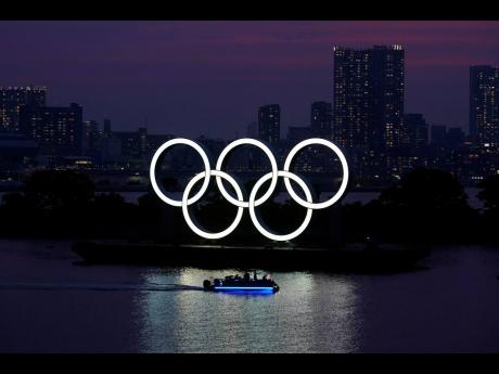 In this June 3, 2020 photo, the Olympic rings float in the water at sunset in the Odaiba section in Tokyo.