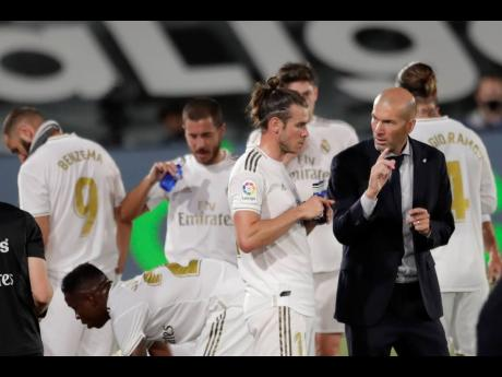 Real Madrid's head coach Zinedine Zidane (right) talks with Real Madrid's Gareth Bale during the Spanish La Liga match against Mallorca at the Alfredo di Stefano Stadium in Madrid, Spain, on Wednesday, June 24.