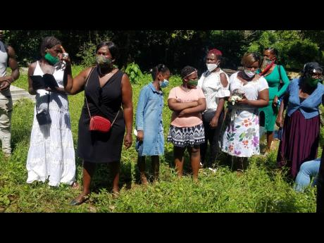 Mourners line up to get one look at Tamara Geddes in the coffin at the cemetery in Reserve, Trelawny.