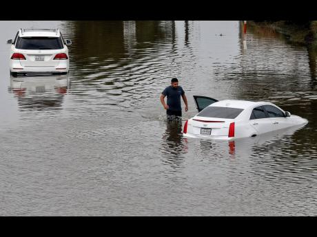 A man checks his vehicle at the intersection of Pearland and South Sam Houston Parkways in Houston, Texas, on Tuesday, following flooding from Tropical Storm Beta.