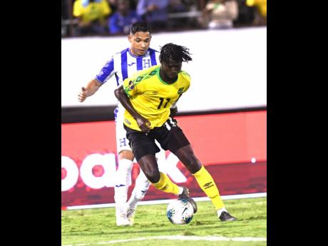 File Jamaica's Shamar Nicholson  dribbles ahead of Honduran player Emilio Izaguirre  in their Concacaf Gold Cup match held at the National Stadium in 2019.