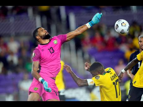Jamaica's goalkeeper Dillon Barnes (13) blocks a shot from a  Costa Rican player during the first half of last night's Concacaf Gold Cup Group C  match in  Orlando, Florida.