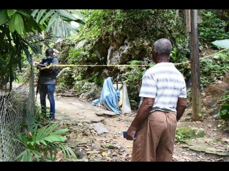 A resident, reportedly the grandfather of one of the victims, looks on as a policeman monitors the cordoned-off crime scene in Hashburn, off Brooks Level Road in Stony Hill.